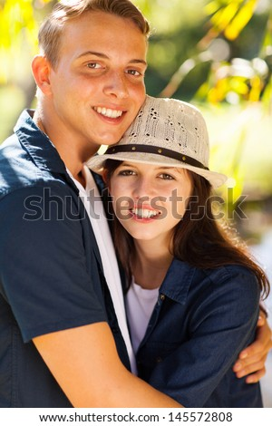 portrait of beautiful young teen couple hugging outdoors