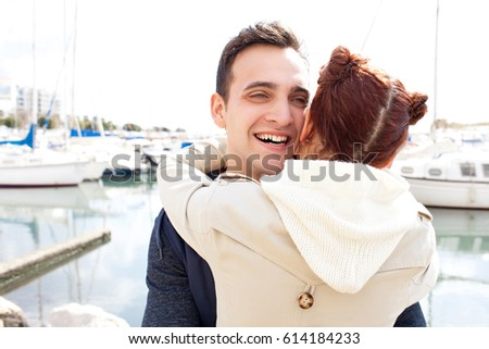 Portrait of beautiful young tourist couple hugging joyful on holiday in port destination with boats, smiling fun, outdoors. Boyfriend and girlfriend in love, travel recreation lifestyle, exterior.