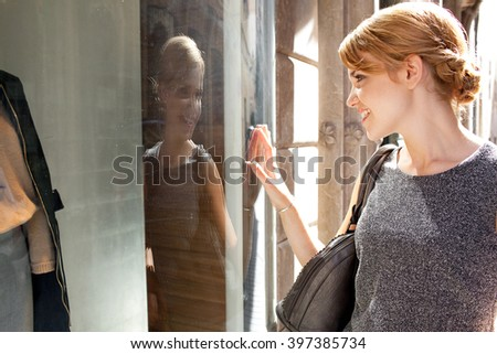 Portrait of beautiful young tourist woman carrying shopping bags in city with fashion stores, joyfully smiling and looking at fashion shop window, outdoors. Consumer exclusive lifestyle exterior. - stock photo