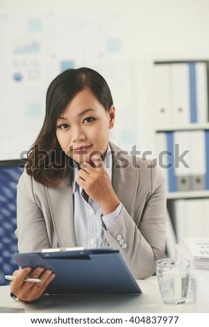 Portrait of beautiful young Vietnamese business lady working in office
