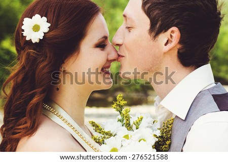 Portrait of beautiful young wedding couple.  Husband kissing him wife in nose. - stock photo