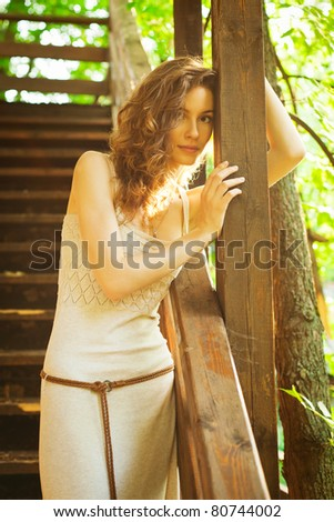 Portrait of beautiful young woman against backdrop of wooden stairs - stock photo