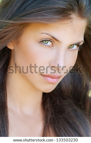 Portrait of beautiful young woman, against summer green park. - stock photo