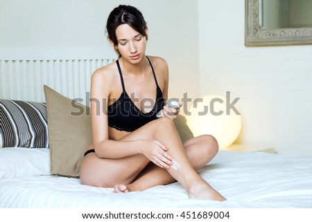 Portrait of beautiful young woman applying body cream on legs. - stock photo