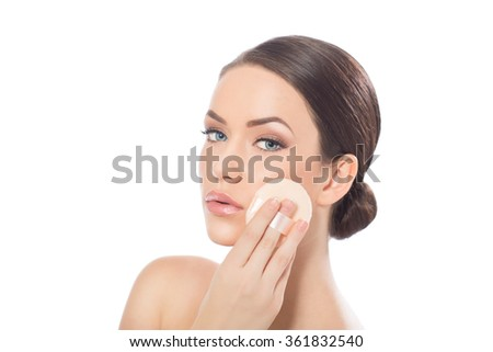 Portrait of beautiful young woman applying foundation, isolated on white - stock photo