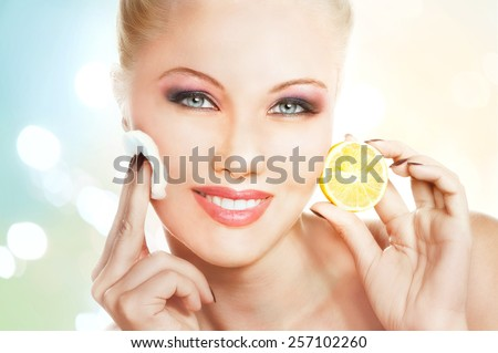 Portrait of beautiful young woman applying lemon facial mask  - stock photo