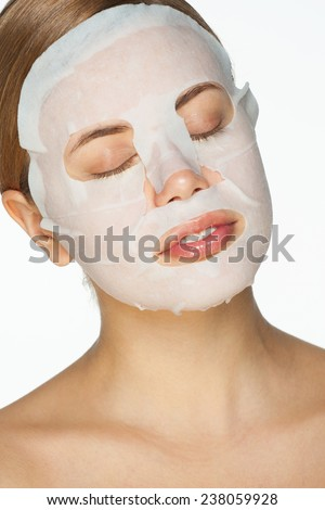Portrait of beautiful young woman applying rejuvenation facial mask on her face - stock photo