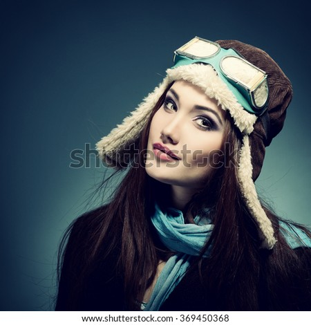 Portrait of beautiful young woman aviator, image toned. - stock photo