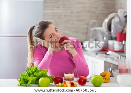 Portrait of beautiful young woman bored with her diet eating an apple while cake is standing in front of her on the table