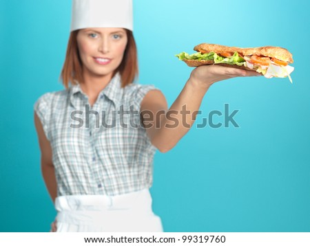 portrait of beautiful young woman chef, holding a big sandwich in one of her hands, on blue background - stock photo