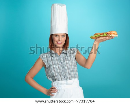 portrait of beautiful young woman chef, holding a big sandwich in one of her hands, on blue background