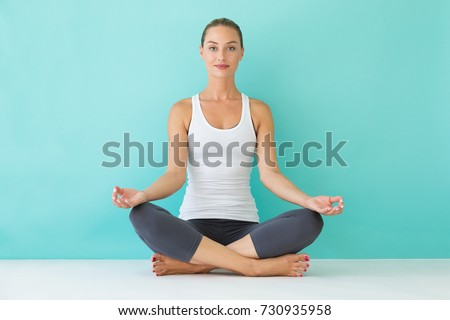 Portrait of beautiful young woman doing yoga at home.