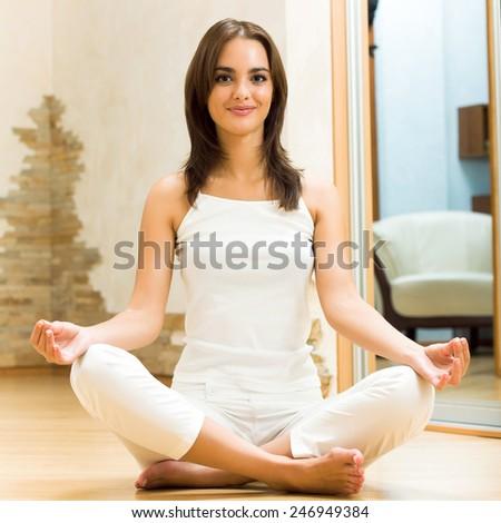 Portrait of beautiful young woman doing yoga exercises, indoors - stock photo