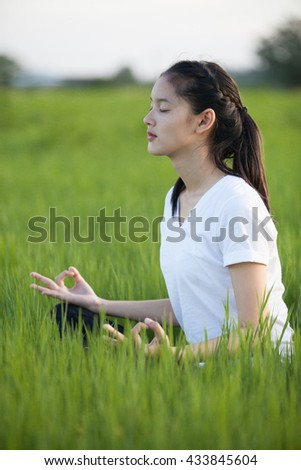 Portrait of beautiful young woman doing yoga in the park