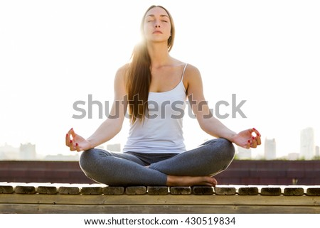 Portrait of beautiful young woman doing yoga in the street. - stock photo