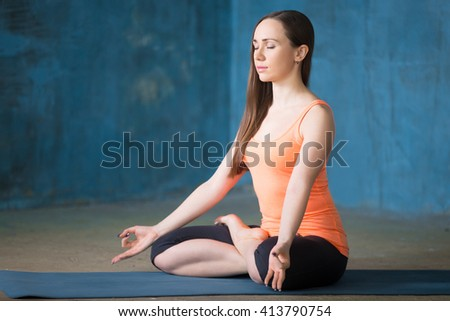 Portrait of beautiful young woman dressed in bright sportswear enjoying yoga indoors. Yogi girl working out in grunge interior with blue wall. Sitting in Half Lotus Posture. Full length - stock photo