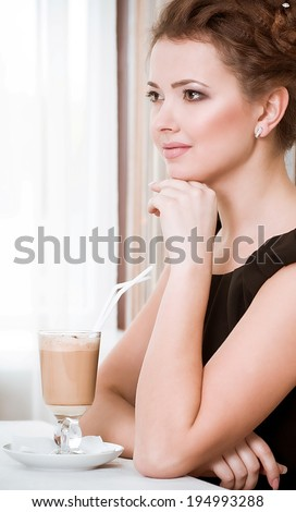 Portrait of beautiful young woman drinking coffee in restaurant - stock photo