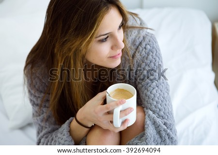 Portrait of beautiful young woman drinking coffee on bed. - stock photo