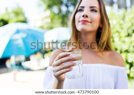 Portrait of beautiful young woman drinking water in the home garden.