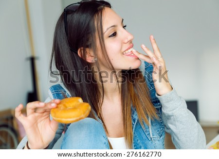 Portrait of beautiful young woman eating donuts at home. - stock photo