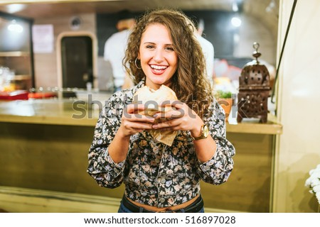 Portrait of beautiful young woman eating hamburguer in the food truck.