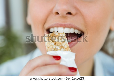 Portrait of beautiful young woman eating muesli snack at home.