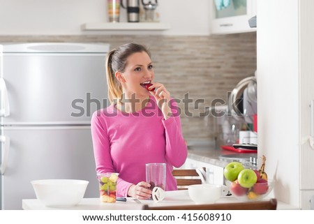 Portrait of beautiful young woman eating strawberries while preparing fruit salad in her kitchen