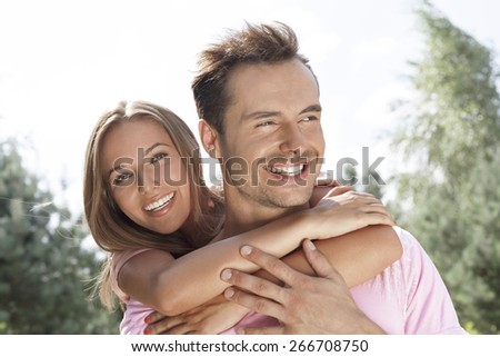 Portrait of beautiful young woman embracing man in summer park - stock photo