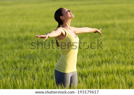 Portrait of beautiful young woman enjoying the spring standing in a cereal field