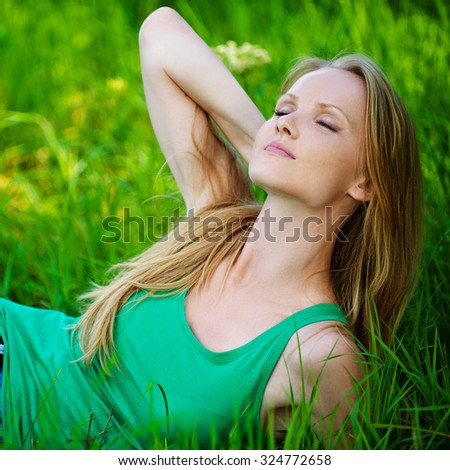 Portrait of beautiful young woman eyes closed lying green grass at summer green park - stock photo