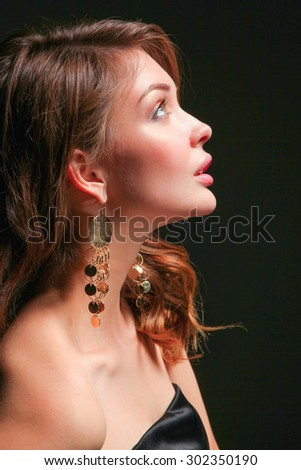 Portrait of beautiful young woman face on dark background.