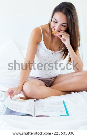 Portrait of beautiful young woman having breakfast and reading magazine on bed.  - stock photo