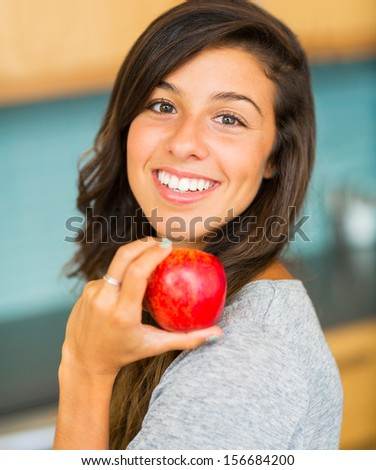 Portrait of beautiful young woman holding a fresh ripe apple and smiling