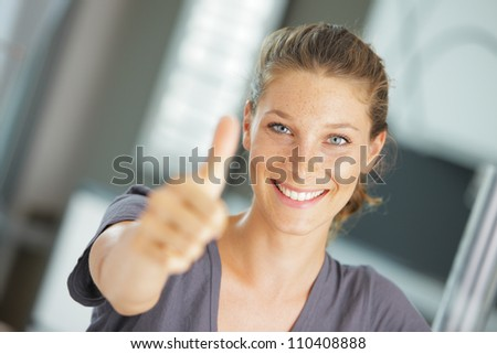 Portrait of beautiful young woman holding a thumbs up to the camera - stock photo