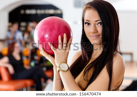 Portrait of beautiful young woman holding pink ball in bowling club