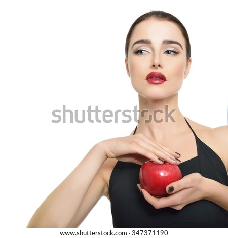 Portrait of beautiful young woman holding red apple and looking at copyspace over white background - stock photo