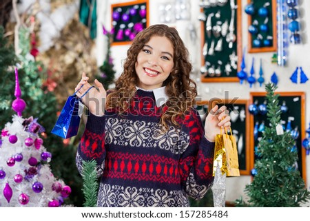 Portrait of beautiful young woman holding small shopping bags at Christmas store - stock photo