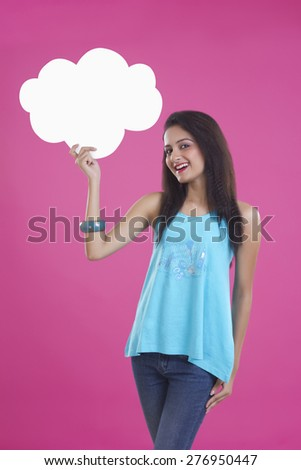 Portrait of beautiful young woman holding thought bubble over pink background