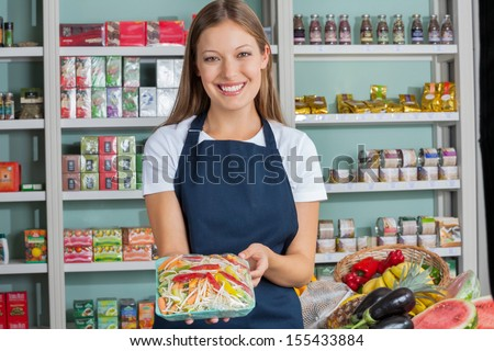 Portrait of beautiful young woman holding vegetable packet in supermarket - stock photo