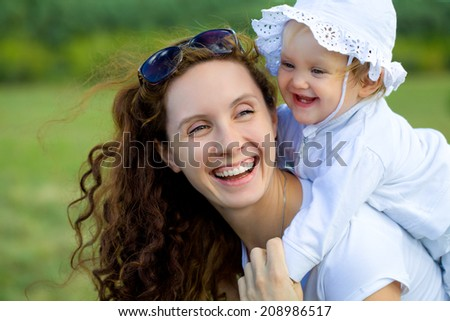Portrait of  beautiful young woman hugging her little baby