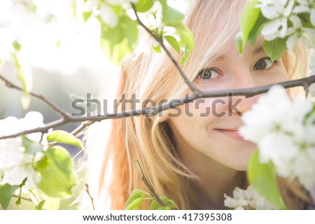 Portrait of beautiful young woman in apple trees blooming park on a sunny day. Smiling girl with apple trees flowers. Happy girl. Happiness concept. - stock photo