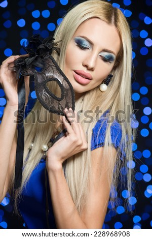 portrait of Beautiful young woman in black mysterious venetian mask. new year carnival - stock photo