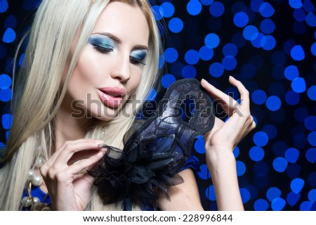 portrait of Beautiful young woman in black mysterious venetian mask. new year carnival