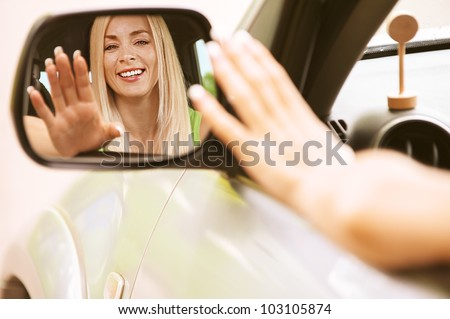 Portrait of beautiful young woman in car is reflected in mirror. - stock photo