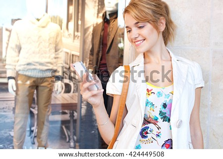 Portrait of beautiful young woman in city shopping street, smiling using smart phone to network outdoors. Tourist woman using technology, travel lifestyle. Shopping mall exterior with clothing store.
