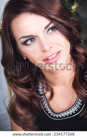 Portrait of beautiful young woman in evening dress over Christmas background. - stock photo