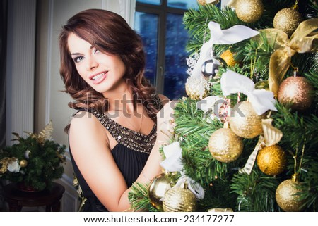 Portrait of beautiful young woman in evening dress over Christmas background.