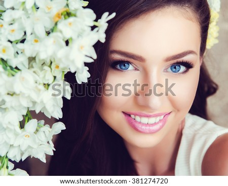 Portrait of Beautiful Young Woman in Flowers. Healthy Long Hair and Clean Skin. Close Up. Vintage Toning - stock photo