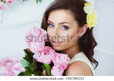 Portrait of Beautiful Young Woman in Flowers. Healthy Long Hair and Clear Skin.