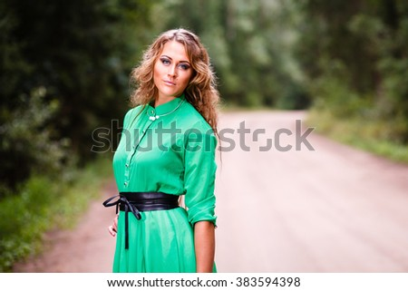 Portrait of beautiful young woman in green dress on water background. - stock photo